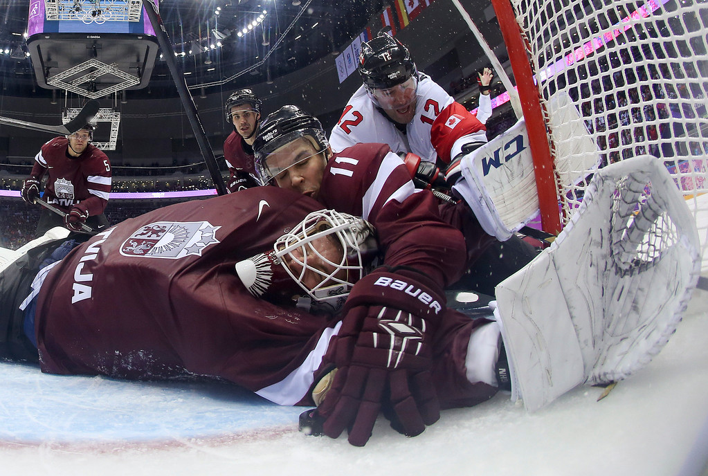. Latvia defenseman Kristaps Sotnieks  reaches over Latvia goaltender Kristers Gudlevskis to grab the puck and keep it from completely crossing the goal line during the third period of a men\'s ice hockey game against Canada at the 2014 Winter Olympics, Wednesday, Feb. 19, 2014, in Sochi, Russia. The goal was disallowed and ruled dead. Canada won 2-1. (AP Photo/Bruce Bennett, Pool)