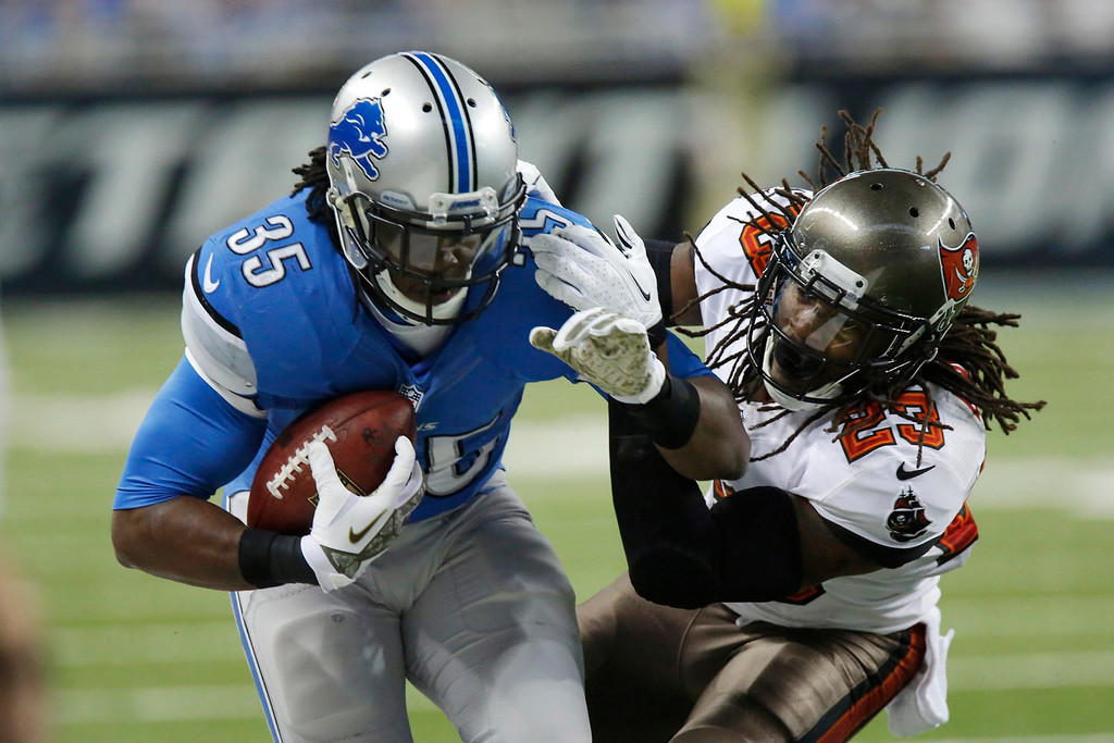 . Detroit Lions running back Joique Bell (35) is stopped by Tampa Bay Buccaneers strong safety Mark Barron (23) during the second quarter of an NFL football game at Ford Field in Detroit, Sunday, Nov. 24, 2013. (AP Photo/Duane Burleson)