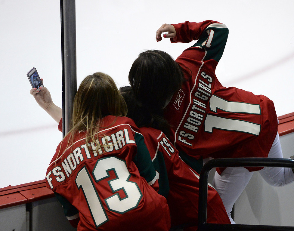 . Three members of the team that cleans the ice in St. Paul took a selfie photo with their faces pressed up against the glass before the game started Thursday night.  (Photo by Karl Gehring/The Denver Post)