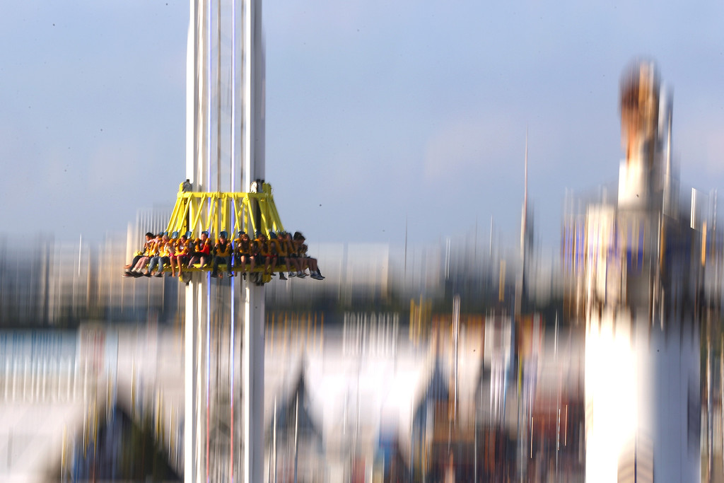 . People enjoy a fairground ride during day 1 of the Oktoberfest 2013 beer festival at Theresienwiese on September 21, 2013 in Munich, Germany. The Munich Oktoberfest, which this year will run from September 21 through October 6, is the world\'s largest beer fest and draws millions of visitors.  (Photo by Alexander Hassenstein/Getty Images)