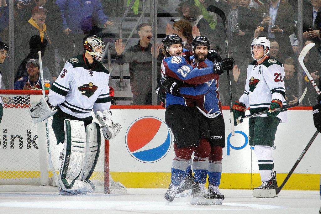 . Colorado Avalanche\'s Nathan MacKinnon (29) hugs Maxime Talbot after he scored during the second period of an NHL hockey game Thursday, Jan. 30, 2014, in Denver. Minnesota Wild goalie Darcy Kuemper, left, and Wild\'s Ryan Suter, right, react in the background. (AP Photo/Barry Gutierrez)