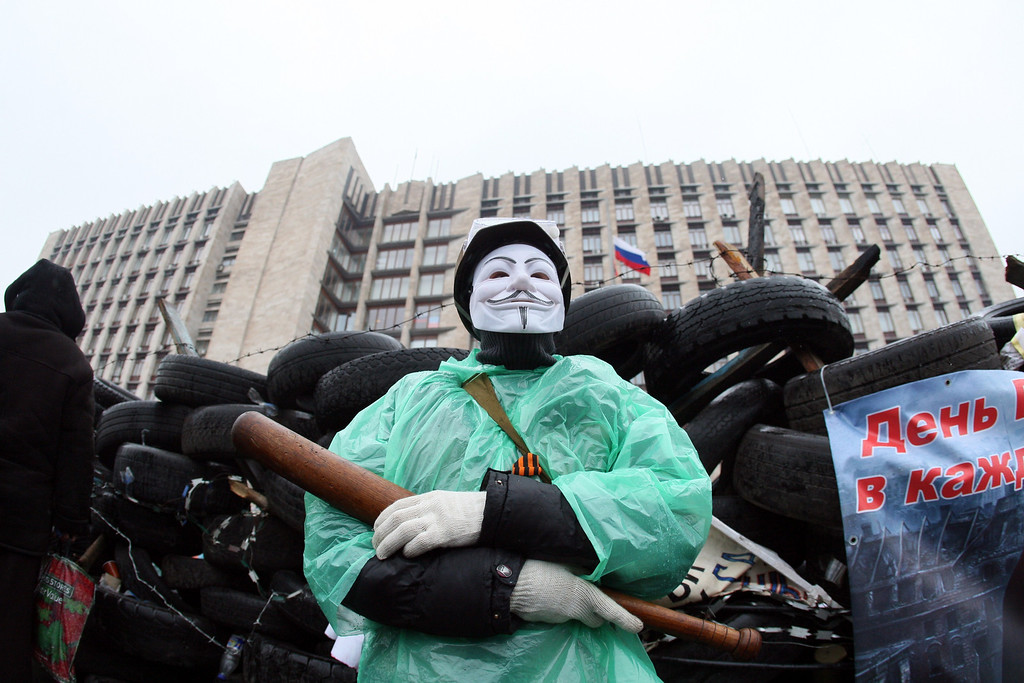 ". A pro-Russian activist wearing a Guy Fawkes mask and holding a bat guards a barricade outside the regional government building in the eastern Ukrainian city of Donetsk on April 13, 2014. Kiev said on April 13 that several had been left ""dead and wounded\"" in fighting to oust pro-Russian gunmen holed up in a police station in the restive east in the city of Slavyansk, as Washington warned Moscow to de-escalate the crisis or face the consequences. AFP PHOTO / ALEXANDER KHUDOTEPLY"