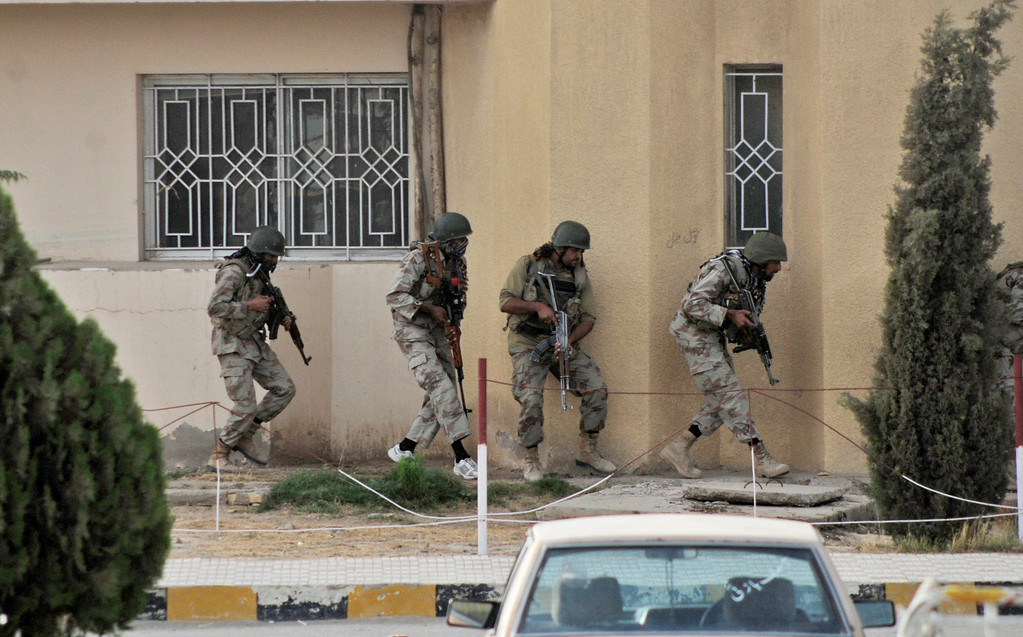 . Pakistani security forces prepare to storm a hospital building during a gun battle in Quetta, Pakistan, Saturday, June 15, 2013.  (AP Photo/Arshad Butt)