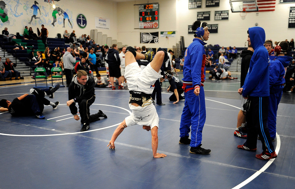 . P.T. Garcia, 18, center, a senior at Bear Creek High School, warms up as he does a headstand before the semifinals round. Photo by Jamie Cotten, Special to The Denver Post
