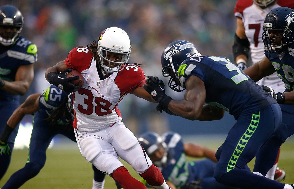 . Andre Ellington #38 of the Arizona Cardinals runs the ball against Kam Chancellor #31 of the Seattle Seahawks on December 22, 2013 at CenturyLink Field in Seattle, Washington.  (Photo by Jonathan Ferrey/Getty Images)