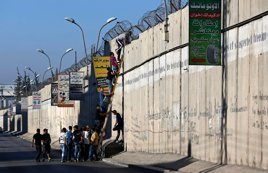 . Palestinian youths, who are not permitted by Israeli security forces to cross into Jerusalem from the West Bank, climb over Israel\'s controversial barrier in the village of Al-Ram, near Ramallah, during the holy month of Ramadan July 26, 2013. Israeli security forces allow only Palestinian males over the age of 40 and under the age of 12 to cross into Jerusalem, while females of all ages are allowed to cross.  REUTERS/Mohamad Torokman