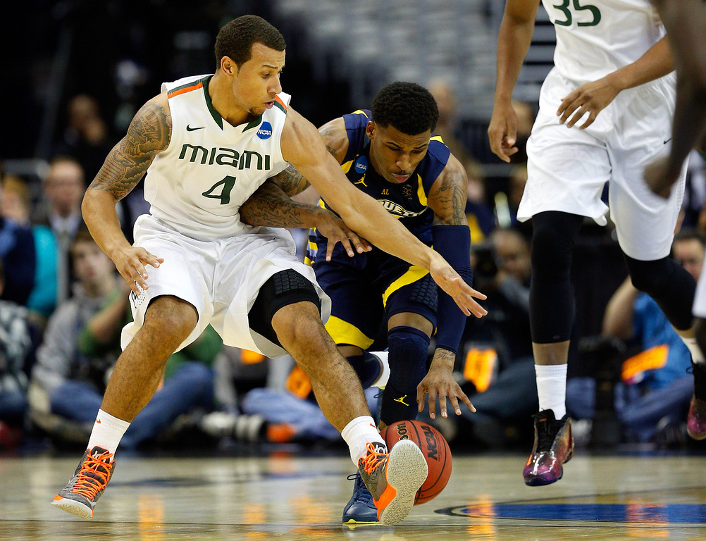 . WASHINGTON, DC - MARCH 28:  Trey McKinney Jones #4 of the Miami (Fl) Hurricanes fights for the loose ball against Junior Cadougan #5 of the Marquette Golden Eagles during the East Regional Round of the 2013 NCAA Men\'s Basketball Tournament at Verizon Center on March 28, 2013 in Washington, DC.  (Photo by Rob Carr/Getty Images)