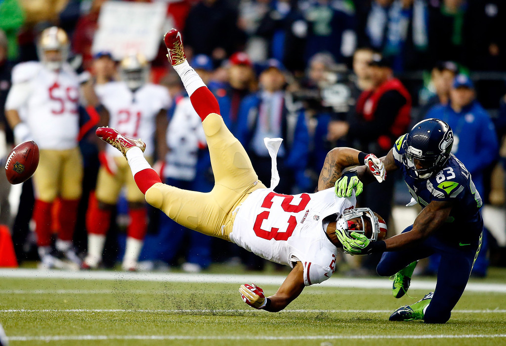 . Kick returner LaMichael James #23 of the San Francisco 49ers is hit by wide receiver Ricardo Lockette #83 of the Seattle Seahawks on a return in the first half during the 2014 NFC Championship at CenturyLink Field on January 19, 2014 in Seattle, Washington.  (Photo by Jonathan Ferrey/Getty Images)