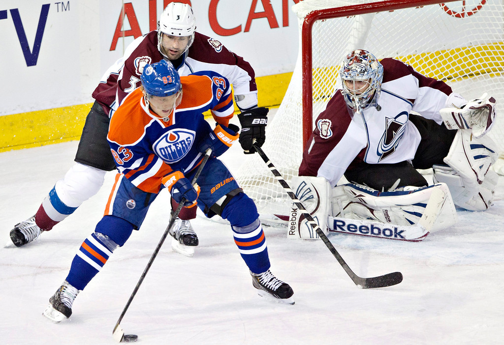 . Edmonton Oilers\' Ales Hemsky (83) looks for a shot on Colorado Avalanche goalie Semyon Varlamov as Avalanche\'s Ryan O\'Byrne defends during the first period of an NHL hockey game in Edmonton, Alberta, on Saturday Feb. 16, 2013. (AP Photo/The Canadian Press, Jason Franson)
