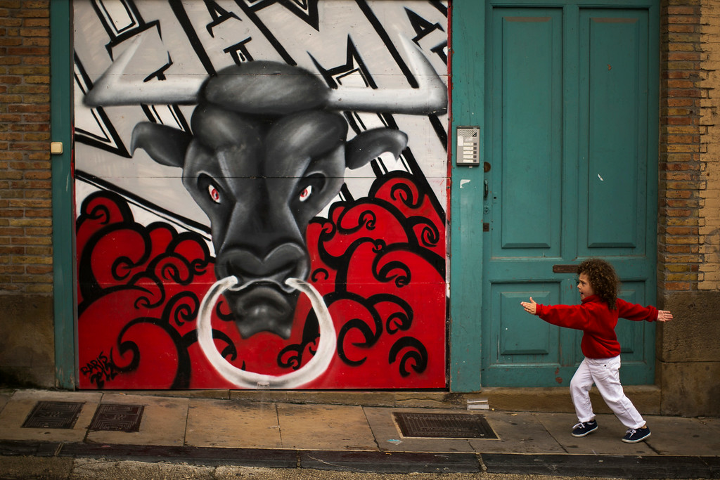 ". A young reveler dressed in a traditional outfit runs next to a mural of a bull during the opening day of the 2014 San Fermin fiestas in Pamplona, Spain, Sunday, July 6, 2014. Revelers from around the world turned out to kick off the festival with a messy party in the Pamplona town square, one day before the first of eight days of the running of the bulls glorified by Ernest Hemingway\'s 1926 novel ""The Sun Also Rises.\"" (AP Photo/Andres Kudacki)"