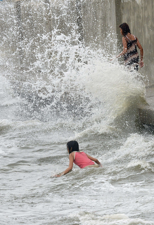 . Young people play in the waves brought on by Typhoon Utor as the ocean splashes up along a sea wall in the suburbs of Manila on August 12, 2013.  The strongest typhoon to hit the Philippines this year flattened houses and triggered landslides in remote towns on August 12, killing at least one person and leaving 23 others missing, authorities said.   JAY DIRECTO/AFP/Getty Images