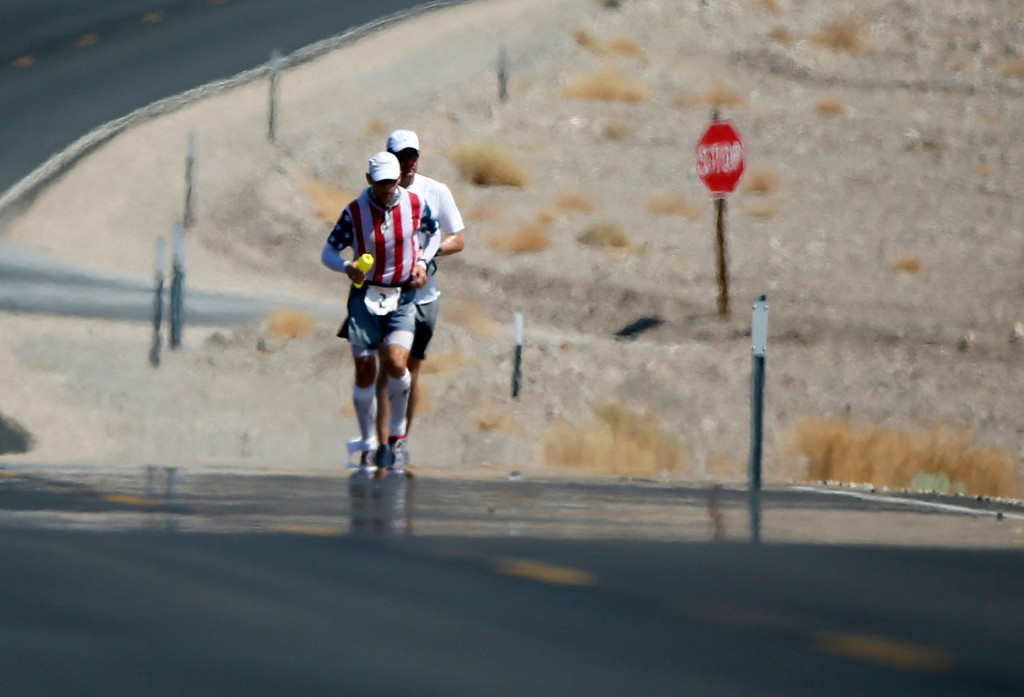 . Charlie Engle, 50, (L) runs through a mirage with his pace setter during the Badwater Ultramarathon in Death Valley National Park, California July 15, 2013. The 135-mile (217 km) race, which bills itself as the world\'s toughest foot race, goes from Death Valley to Mt. Whitney, California in temperatures which can reach 130 degrees Fahrenheit (55 Celsius).  REUTERS/Lucy Nicholson
