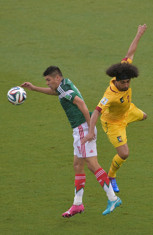 . Cameroon\'s defender Benoit Assou-Ekotto (R) challenges Mexico\'s forward Oribe Peralta during the Group A football match between Mexico and Cameroon at the Dunas Arena in Natal during the 2014 FIFA World Cup on June 13, 2014. AFP PHOTO / GABRIEL BOUYS/AFP/Getty Images