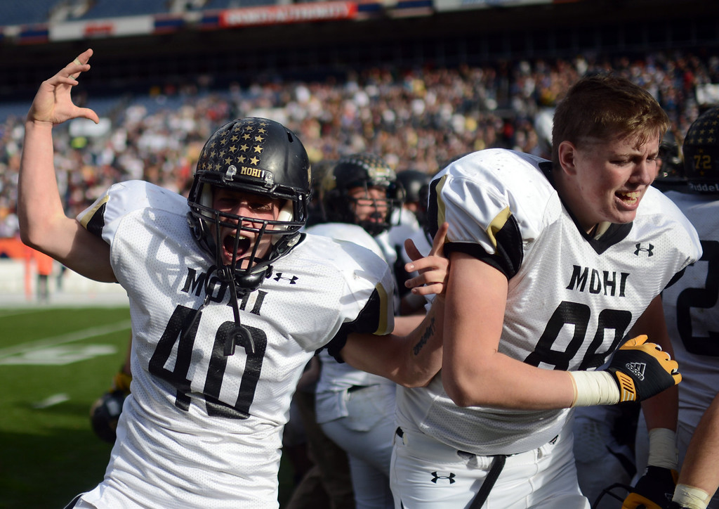 . Monarch Dylan Glazer, left, celebrates the team\'s 17-14 win over Denver South in the 4A State Championship game a Sports Authority Field at Mile High in Denver on Saturday, December 1, 2012.   Hyoung Chang, The Denver Post