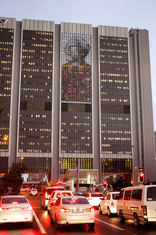 . A portrait, center rear, representing former South African President Nelson Mandela is displayed on the windows of a building as lights inside the building reflect in downtown Cape Town, South Africa, Thursday,  July 18, 2013.  South Africa celebrated Nelson Mandela\'s 95th birthday on Thursday, a milestone capped by news that the former president\'s health was improving after fears that he was close to death during ongoing hospital treatment. (AP Photo/Schalk van Zuydam)