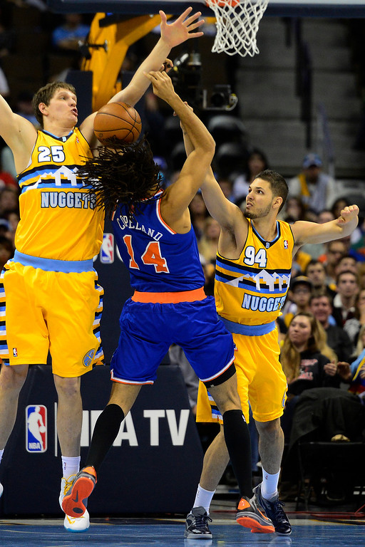 . DENVER, CO - MARCH 13: Evan Fournier (94) of the Denver Nuggets fouls Chris Copeland (14) of the New York Knicks as Timofey Mozgov assists during the second half of of the Nuggets\' win. The Denver Nuggets play the New York Knicks at the Pepsi Center. (Photo by AAron Ontiveroz/The Denver Post)