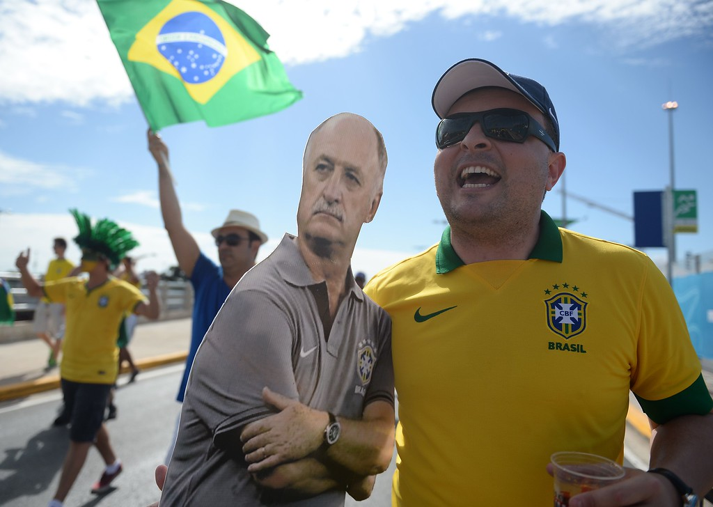 . TOPSHOTS  A Brazilian supporter holds a board depecting Brazil\'s coach Luiz Felipe Scolari outside the Castelao Stadium in Fortaleza before a quarter-final football match between Brazil and Colombia during the 2014 FIFA World Cup on July 4, 2014.  AFP PHOTO / EITAN ABRAMOVICHEITAN ABRAMOVICH/AFP/Getty Images