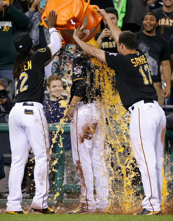 . Pittsburgh Pirates\' Jordy Mercer, center, is doused by teammates Andrew McCutchen, left, and Gaby Sanchez, right, as he is interviewed after hitting a walk off double off Colorado Rockies relief pitcher Chad Bettis during the 11th inning of a baseball game in Pittsburgh Saturday, July 19, 2014. The Pirates won in 3-2 in 11 innings. (AP Photo/Gene J. Puskar)