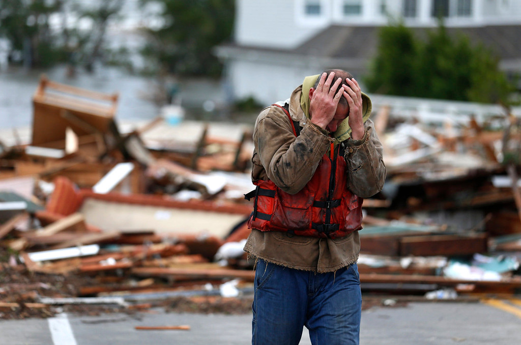 . Brian Hajeski, 41, of Brick, N.J., reacts after looking at debris of a home that washed up on to the Mantoloking Bridge the morning after superstorm Sandy rolled through, Tuesday, Oct. 30, 2012, in Mantoloking, N.J. Sandy, the storm that made landfall Monday, caused multiple fatalities, halted mass transit and cut power to more than 6 million homes and businesses. (AP Photo/Julio Cortez)