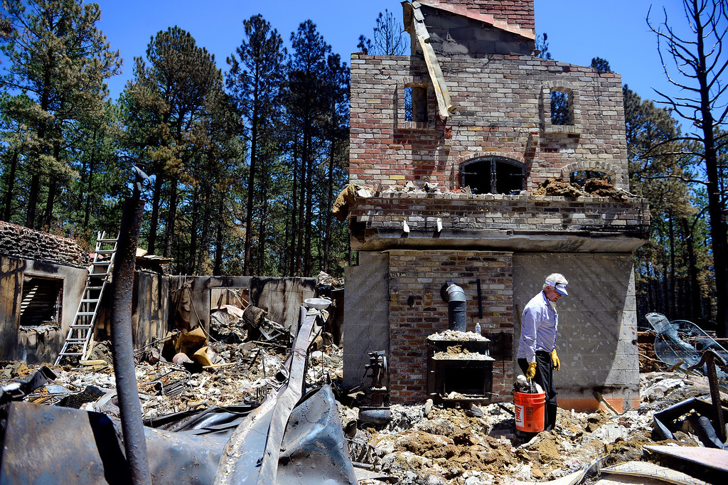 . BLACK FOREST, CO - JUNE 19: Don Burgess looks through the remnants of his home after it was burned by the Black Forest Fire on Shoup Road. Burgess, and his wife, Vaneal, owned the home for 35 years, raised their children and entertained their 13 grandchildren. Their daughter also lost her home to the Black Forest Fire near Herring Road. (Photo by AAron Ontiveroz/The Denver Post)