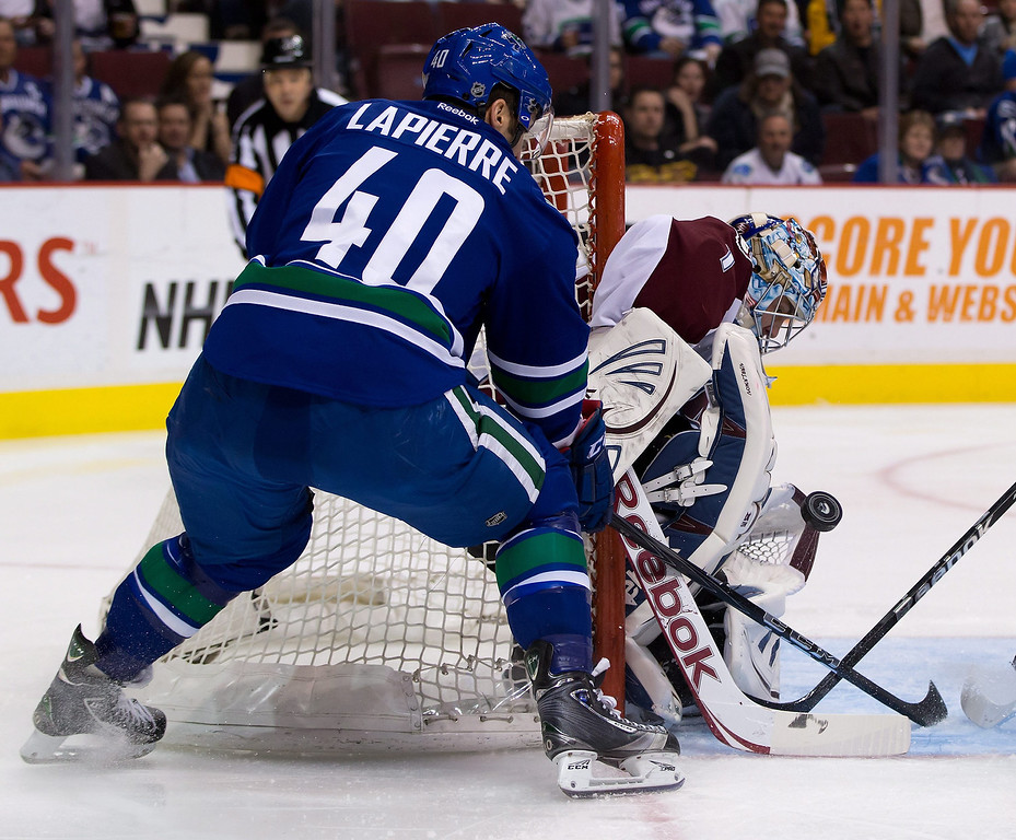 . Vancouver Canucks\' Maxim Lapierre, left, is stopped by Colorado Avalanche goalie Semyon Varlamov, of Russia, during the first period of an NHL hockey game in Vancouver, British Columbia, Thursday, March 28, 2013. (AP Photo/The Canadian Press, Darryl Dyck)