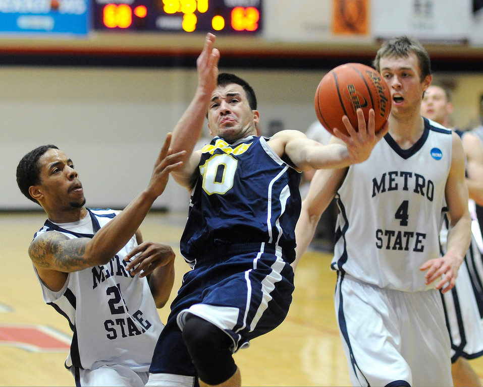 . DENVER, CO. - MARCH 5: Cougars junior guard Kyle Weaver (10) cut between Metro State\'s Demetrius Miller (24) and Nicholas Kay (4) in the second half. The Metro State University of Denver men\'s basketball team defeated Colorado Christian University 87-75 Tuesday night, March 5, 2013. (Photo By Karl Gehring/The Denver Post)