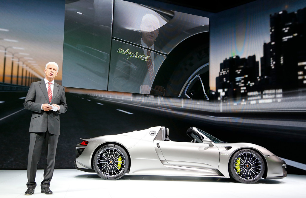 . Porsche CEO Matthias Mueller presents the Porsche 918 hybrid sports car during the first press day of the 65th Frankfurt Auto Show in Frankfurt, Germany, Tuesday, Sept. 10, 2013. (AP Photo/Frank Augstein)