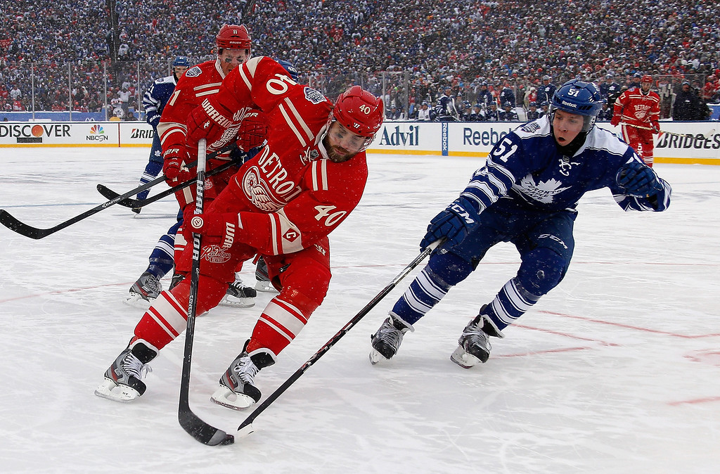 . Jake Gardiner #51 of the Toronto Maple Leafs defends Henrik Zetterberg #40 of the Detroit Red Wings during the 2014 Bridgestone NHL Winter Classic at Michigan Stadium on January 1, 2014 in Ann Arbor, Michigan. Toronto won the game 3-2 in a shootout. (Photo by Gregory Shamus/Getty Images)