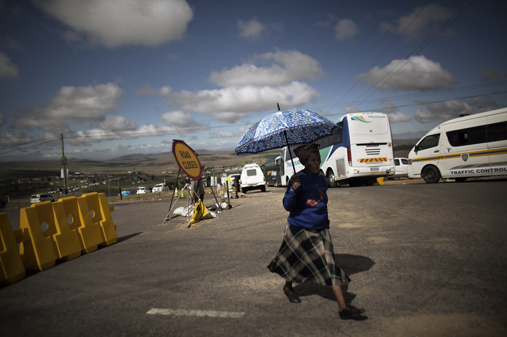 . A woman walks past a closed road sign near the location of the funeral ceremony of South African former president Nelson Mandela in Qunu on December 15, 2013. South Africa\'s first black president Nelson Mandela received a tearful state funeral at his childhood village of Qunu on Sunday, followed by a traditional burial attended by family and friends. Mandela, the revered icon of the anti-apartheid struggle in South Africa and one of the towering political figures of the 20th century, died in Johannesburg on December 5 at age 95.  AFP PHOTO / MARCO LONGARIMARCO LONGARI/AFP/Getty Images