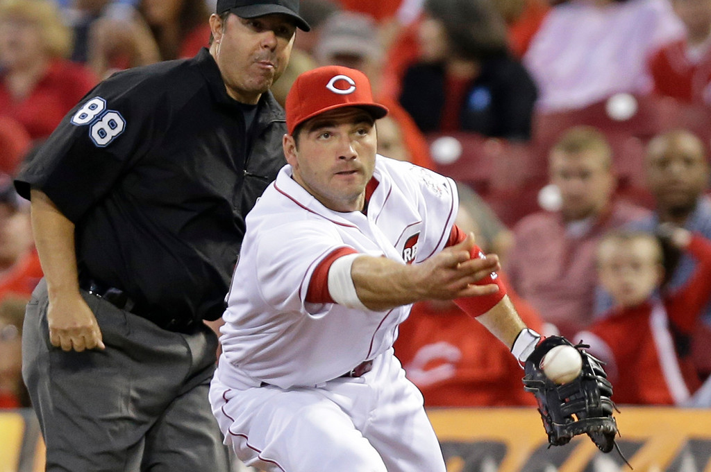 . Cincinnati Reds first baseman Joey Votto tosses the ball to first base for the out after fielding a ground ball hit by Colorado Rockies\' Justin Morneau in the fifth inning of a baseball game on Saturday, May 10, 2014, in Cincinnati. Umpire Doug Eddings (88) watches the play. (AP Photo/Al Behrman)