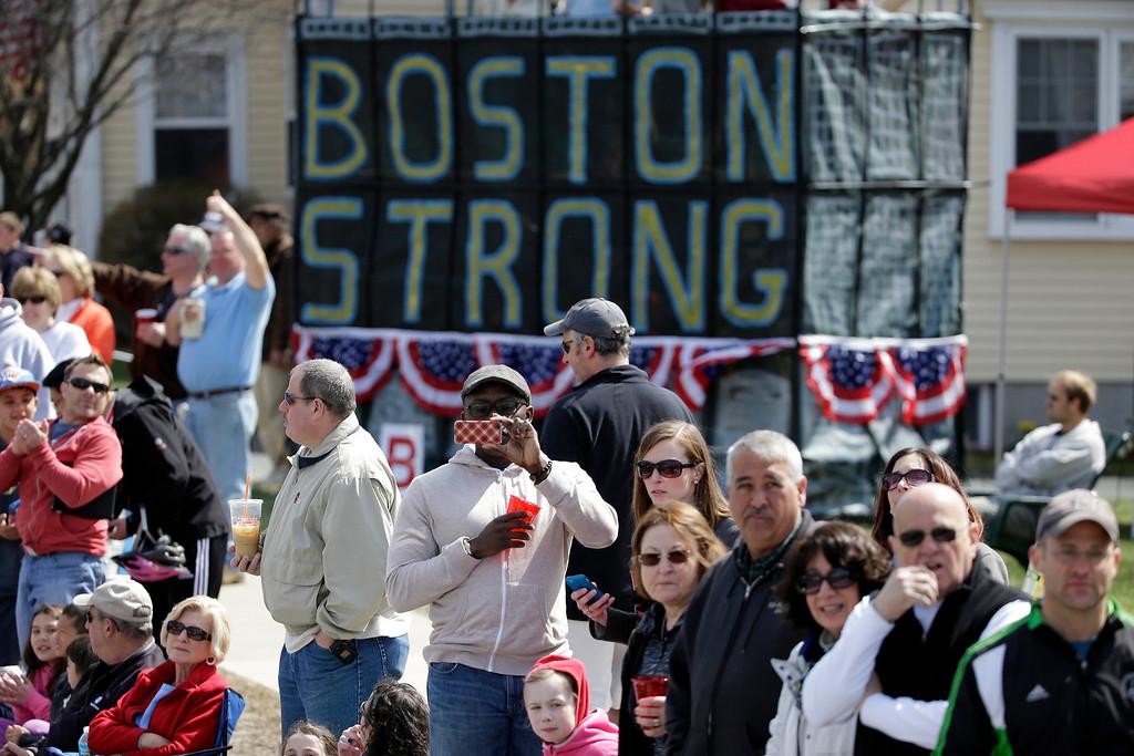 """. Race fans alongside a \""""Boston Strong\"""" slogan, watch the 118th Boston Marathon Monday, April 21, 2014 along the race course to Boston. (AP Photo/Steven Senne)"""