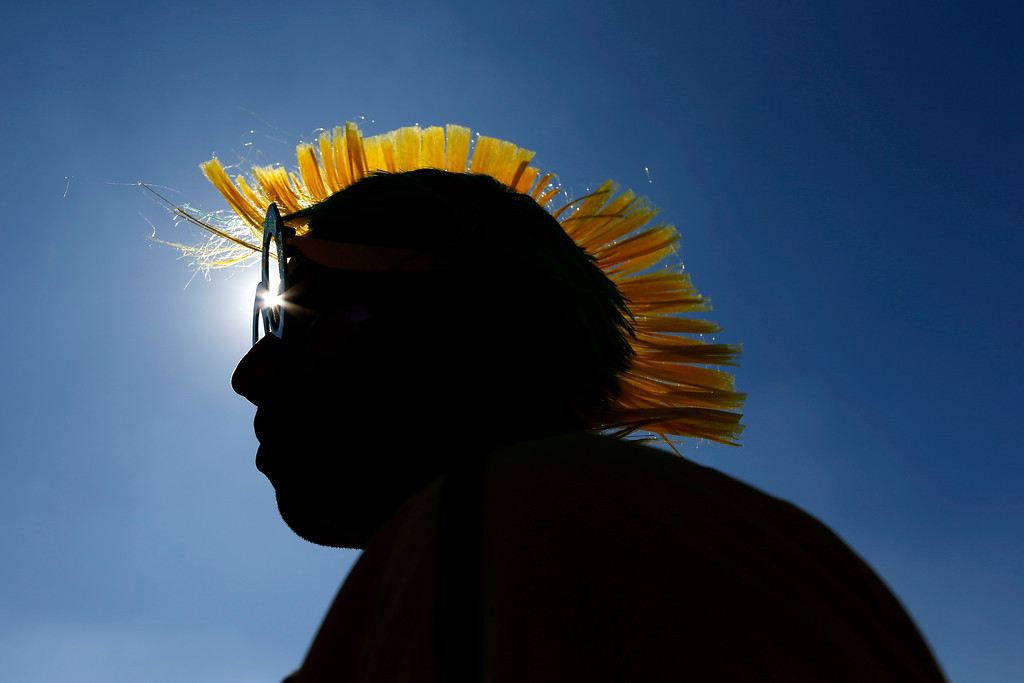 ". Brazilian Marcelo Bora, 22, and his mohawk-styled wig, are silhouetted against a blue sky as he waits to enter the Itaquerao Stadium to watch the World Cup opening match, between Brazil and Croatia of group A, in Sao Paulo, Brazil, Thursday, June 12, 2014. Thursday is a holiday in Sao Paulo and everybody is celebrating the start of the international soccer tournament. Fans dressed in yellow and green greeted each other, often yelling, ""Vai Brazil!\""  (AP Photo/Julio Cortez)"