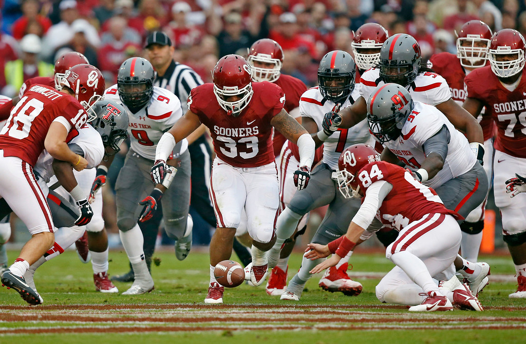 . Texas Tech\'s Branden Jackson (9) and Kerry Hyder (91) and Oklahoma\'s Michael Hunnicutt (18) Trey Millard (33) and Mike Onuoha (84) chase a loose ball after a blocked Oklahoma kick in the first quarter of an NCAA college football game in Norman, Okla., Saturday, Oct. 26, 2013. (AP Photo/Sue Ogrocki)