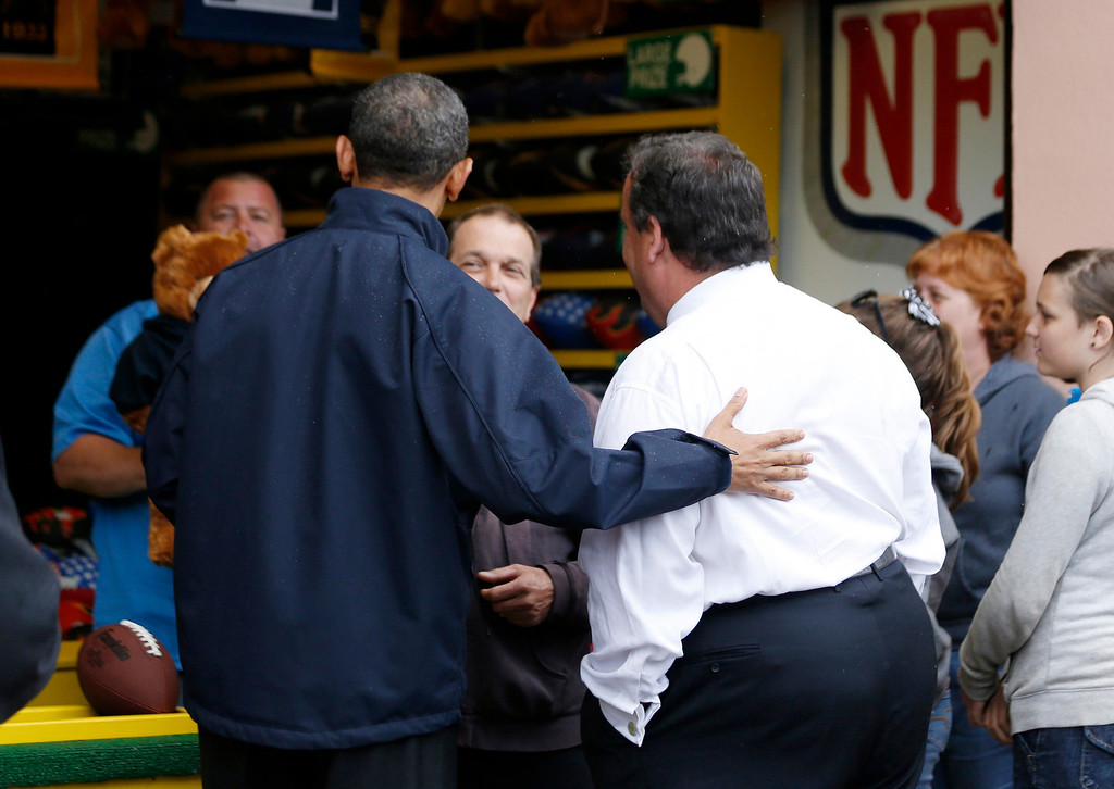 . U.S. President Barack Obama and New Jersey Governor Chris Christie pick out a teddy bear won during a sideshow arcade game on the boardwalk at Point Pleasant in New Jersey, May 28, 2013.   REUTERS/Jason Reed