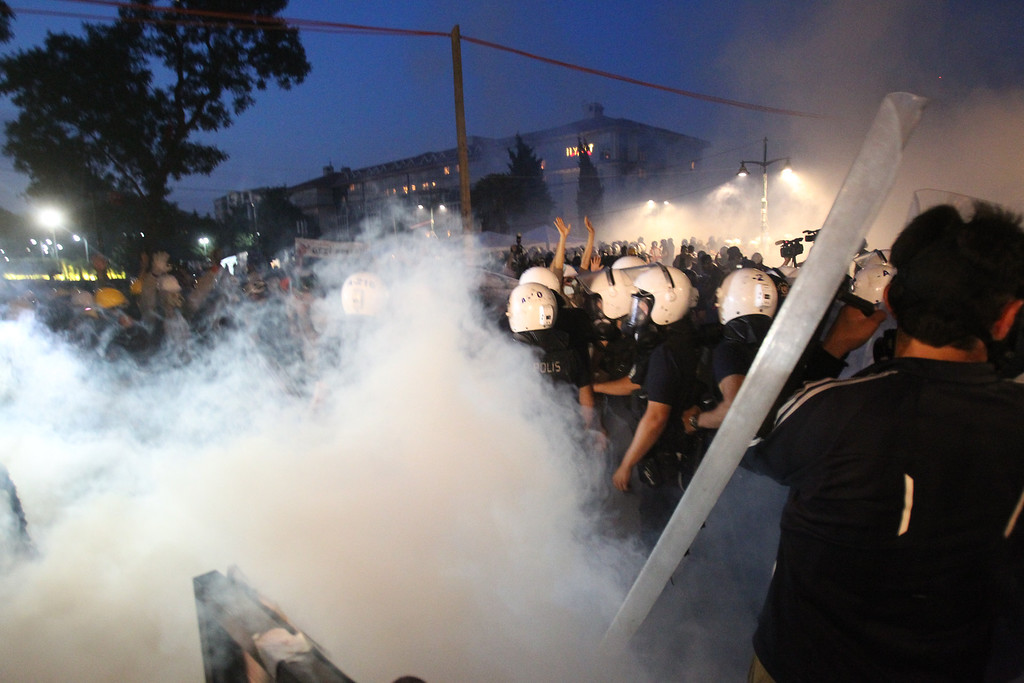 """. Police throw tear gas during clashes as they try to evacuate protestors from the Gezi Park  in Istanbul, Saturday,  June 15, 2013. Riot police fired water cannons and tear gas as they drove protesters out of Istanbul\'s Taksim Square and neighboring Gezi Park on Saturday, an intervention that came shortly after the prime minister warned that security forces \""""know how to clear\"""" the area, which had become a symbol of the biggest anti-government protests in decades. (AP Photo/Thanassis Stavrakis)"""