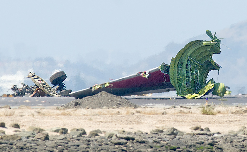 . The detached tail and landing gear of Asiana Flight 214 rest on the tarmac after the plane crashed at San Francisco International Airport on Saturday, July 6, 2013, in San Francisco. (AP Photo/Noah Berger)