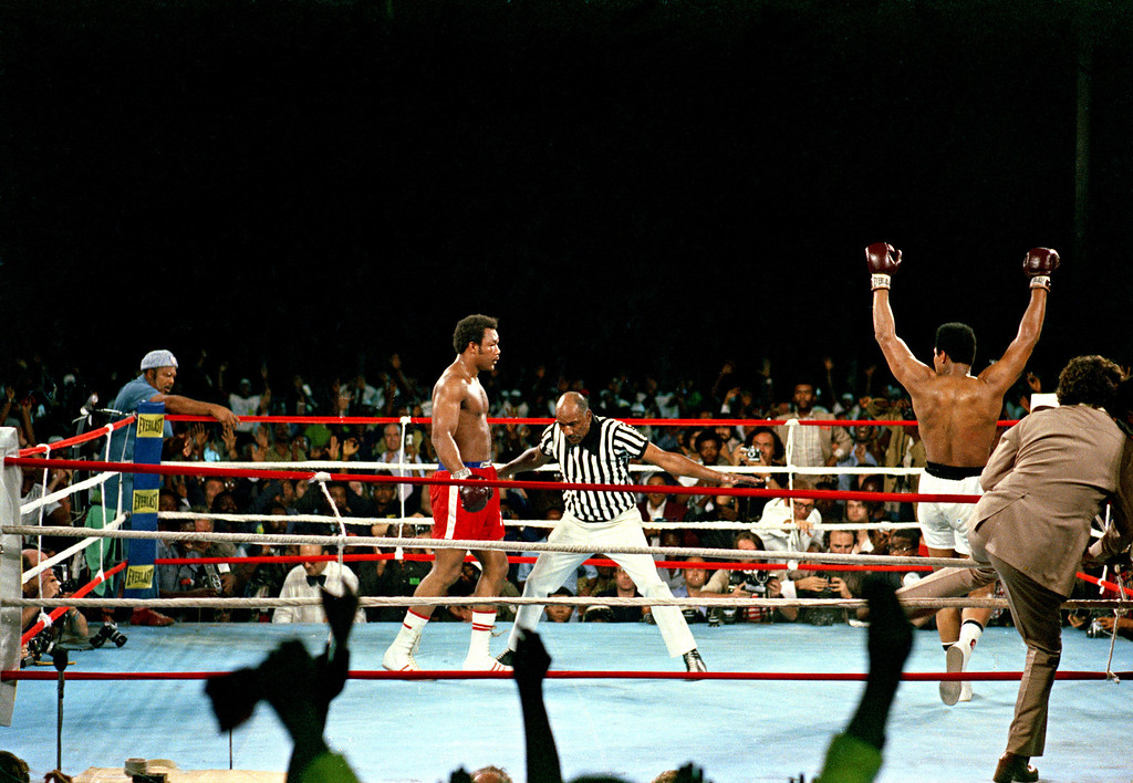 . Challenger Muhammad Ali raises his arms in victory after defending champion George Foreman is counted out by referee Zack Clayton, ending the WBA/WBC championship bout in Kinshasa, Zaire, on October 30, 1974. Ali regains the crown as the undisputed heavyweight world champion by KO in the eighth round of their fight dubbed \'Rumble in the Jungle.\'  (AP Photo)