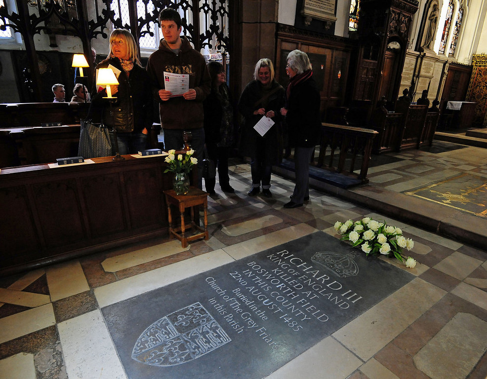 """. People stand near the memorial stone to King Richard III, inside Leicester Cathedral, England, Monday Feb. 4, 2013. Leicester University declared Monday that the remains  found underneath a car park last September at the Grey Friars excavation in Leicester, were \""""beyond reasonable doubt\"""" to be the long lost remains of England\'s King Richard III, missing for 500 years.  Richard was immortalized in a play by  Shakespeare as a hunchbacked usurper who left a trail of bodies including those of his two young nephews, murdered in the Tower of London on his way to the throne.(AP Photo/PA, Rui Vieira)"""