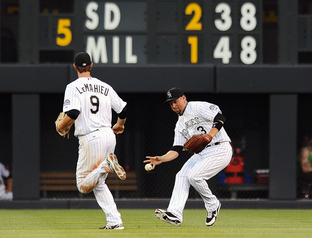 . A hit by Miami Marlins Jeff Mathis drops between Colorado Rockies second baseman DJ LeMahieu, left, and right fielder Michael Cuddyer in the fifth inning of a baseball game Tuesday, July 23, 2013 in Denver. (AP Photo/Chris Schneider)