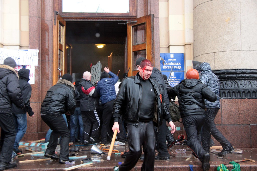 . An injured man carries a baton as pro-Russian activists clash with Maidan supporters as they storm the regional government building in Kharkiv on March 1, 2014.  AFP PHOTO/ SERGEY BOBOK/AFP/Getty Images