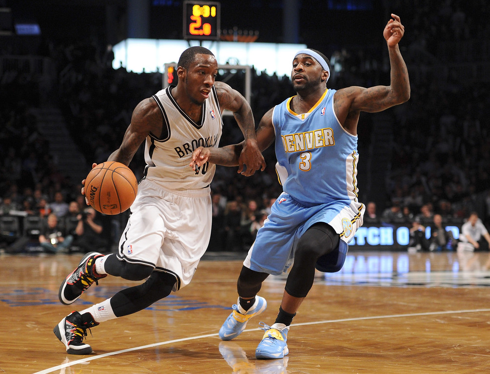 . NEW YORK, NY - DECEMBER 03:  Tyshawn Taylor #10 of the Brooklyn Nets drives against Ty Lawson #3 of the Denver Nuggets during the second half at Barclays Center on December 3, 2013 in the Brooklyn borough of New York City. The Nuggets defeat the Nets 111-87.  (Photo by Maddie Meyer/Getty Images)