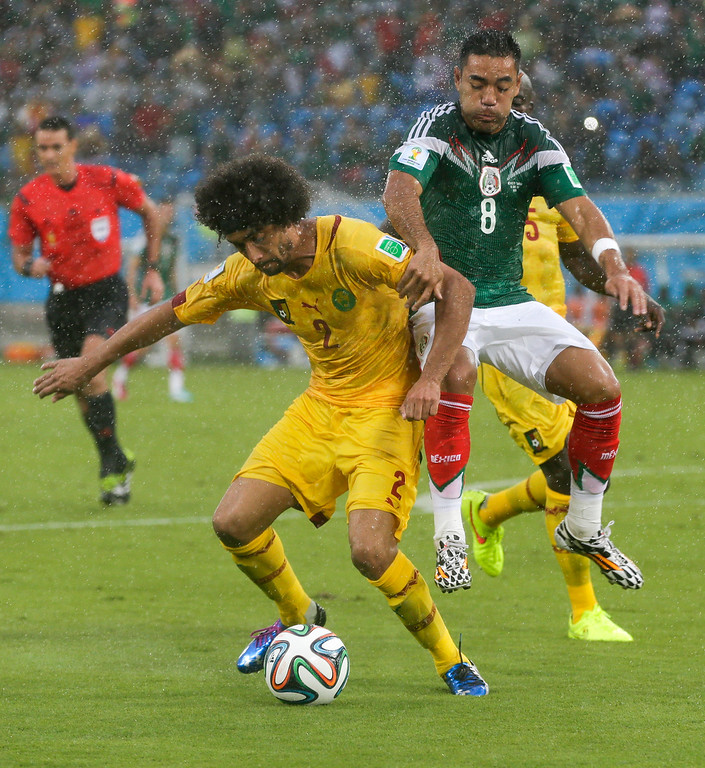 . Mexico\'s Marco Fabian (8) attempts to pull Cameroon\'s Benoit Assou-Ekotto (2) from the ball during the second half of the group A World Cup soccer match between Mexico and Cameroon in the Arena das Dunas in Natal, Brazil, Friday, June 13, 2014.  (AP Photo/Petr David Josek)