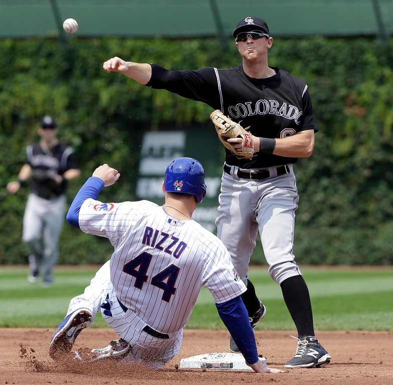 . Colorado Rockies second baseman D.J. LeMahieu, right, throws out Chicago Cubs\' Starlin Castro at first base after forcing out Anthony Rizzo at second base during the first inning of a baseball game in Chicago, Thursday, July 31, 2014. (AP Photo/Nam Y. Huh)