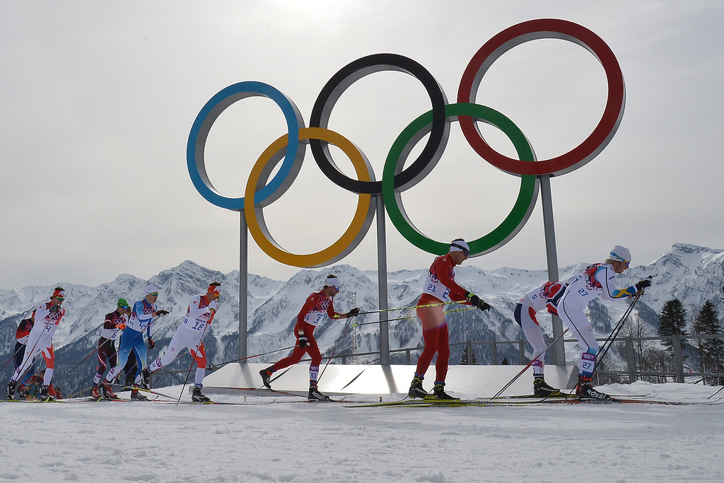 . Switzerland\'s Dario Cologna (21center) skis past the Olympic rings as he competes in the Men\'s Cross-Country Skiing 15km + 15km Skiathlon at the Laura Cross-Country Ski and Biathlon Center during the Sochi Winter Olympics on February 9, 2014, in Rosa Khutor. Others are Sweden\'s Lars Nelson (27), Norway\'s Petter Jr Northug (5), Switzerland\'s Curdin Perl (31), Canada\'s Ivan Babikov (18), Finland\'s Iivo Niskanen (44), Austria\'s Johannes Duerr (6) and Canada\'s Alex Harvey (4).   ALBERTO PIZZOLI/AFP/Getty Images
