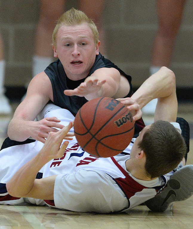 . LITTLETON, CO. - JANUARY 17: Chatfield guard Austin Rice (20) and Dakota Ridge point Ian MacDonald (21) went to the court scrambling for a loose ball in the first half. The Dakota Ridge High School boy\'s basketball team hosted Chatfield Friday night, January 16, 2014. Photo By Karl Gehring/The Denver Post