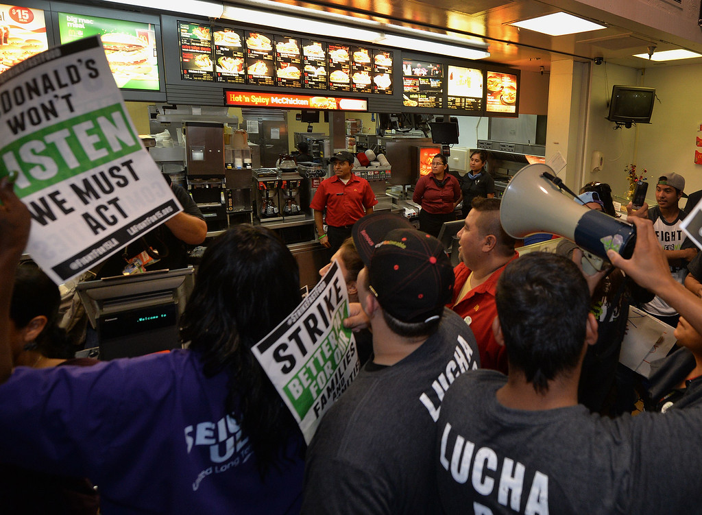 . Fast food workers protest inside a McDonald\'s restaurant during a demonstration against low wages in Los Angeles on September 04, 2014.  A dozen protesters were arrested during the demonstration which  is part of a series of nationwide protests calling for higher wages for fast-food restaurant workers.       AFP PHOTO/Mark RALSTONMARK RALSTON/AFP/Getty Images