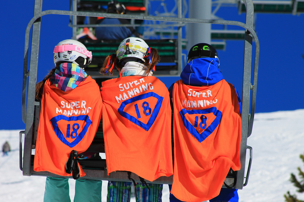 . Justin,Ciara, and Lindsey wear their Super Manning capes as they ride up the lift.