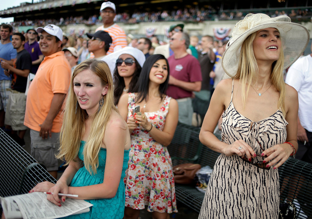 . Racing fans react as horses approach the finish line during a race at Belmont Park Saturday, June 8, 2013, in Elmont, N.Y.  The Belmont Stakes will be run at the park later in the day. (AP Photo/Seth Wenig)
