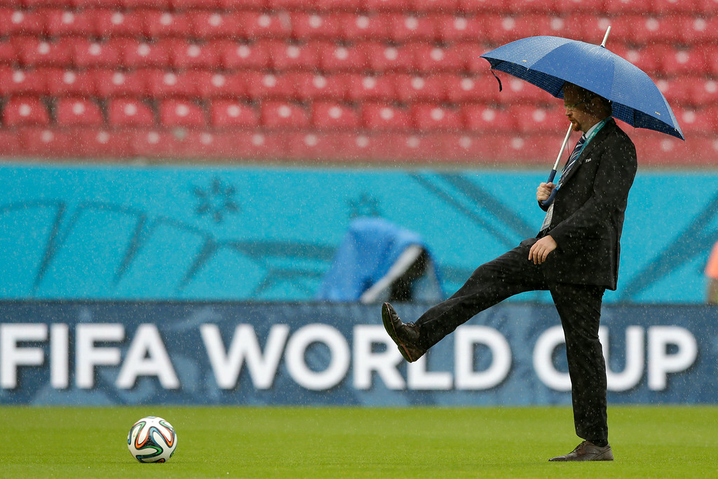 . A FIFA official tests the pitch as rain pours down prior to the group G World Cup soccer match between the USA and Germany at the Arena Pernambuco in Recife, Brazil, Thursday, June 26, 2014. (AP Photo/Matthias Schrader)