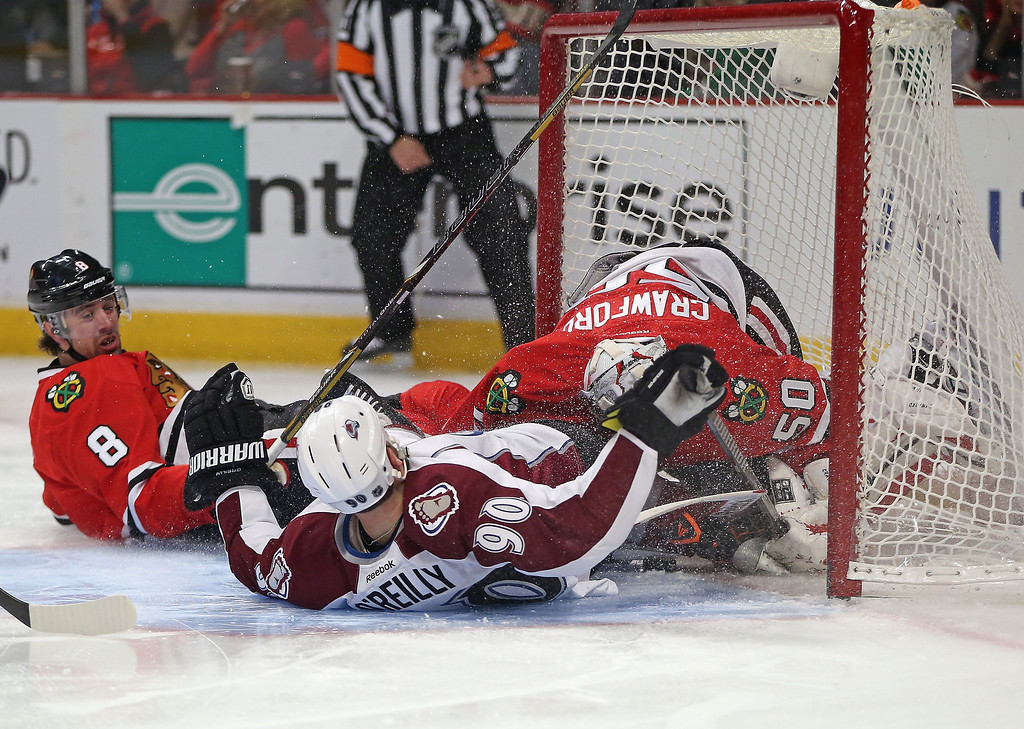 . Ryan O\'Reilly #90 of the Colorado Avalanche crashes into Corey Corawford #50 of the Chicago Blackhawks after being taken down by Nick Leddy #8 at the United Center on January 14, 2014  in Chicago, Illinois. (Photo by Jonathan Daniel/Getty Images)